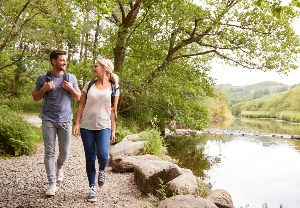 couple walking and talking in woodland next to the lake