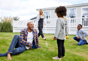 family relaxing and play on the grass in front of their holiday home