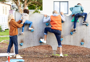 family of four climbing a small climbing wall, children getting helped by mum and dad
