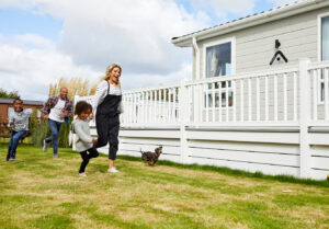 family running on the grass next to their holiday home with their dog