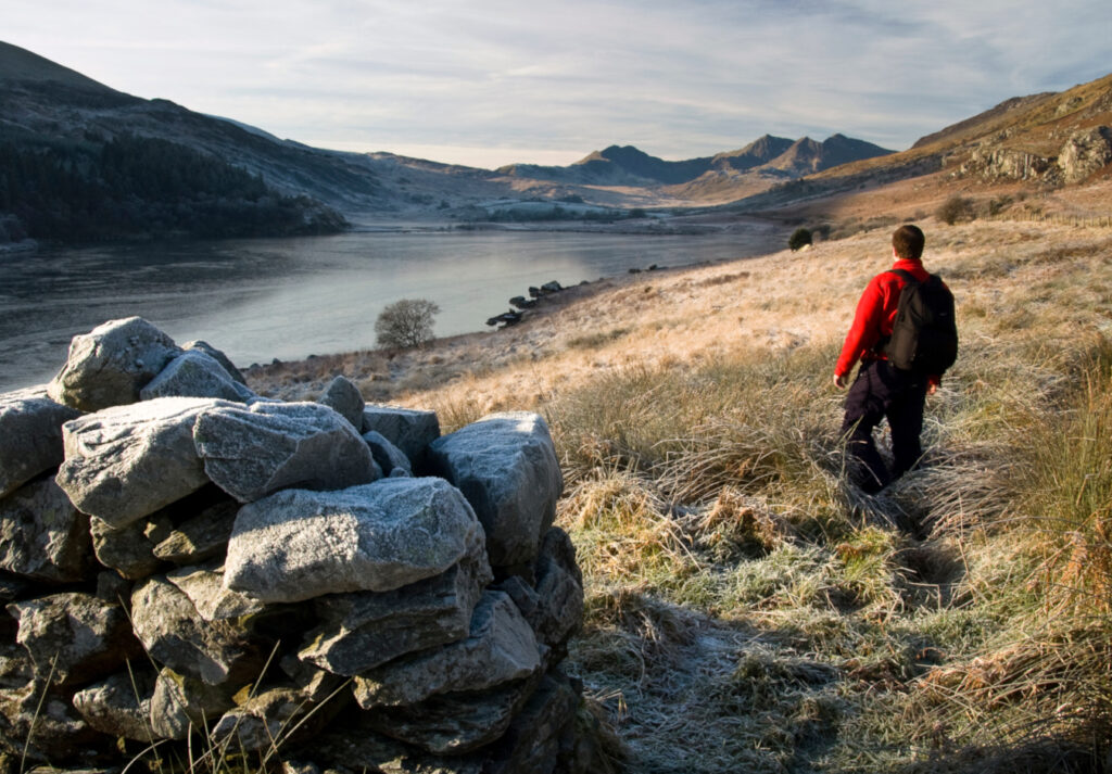 man standing on a hill overlooking a great lake in the lake district