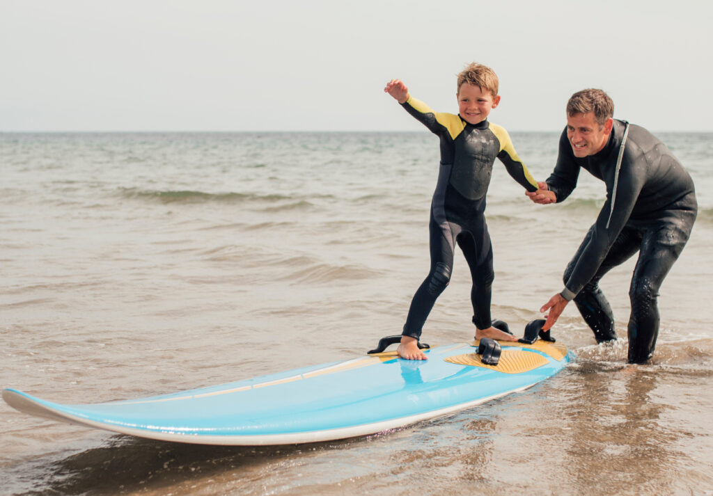 man teaching young boy how to surf