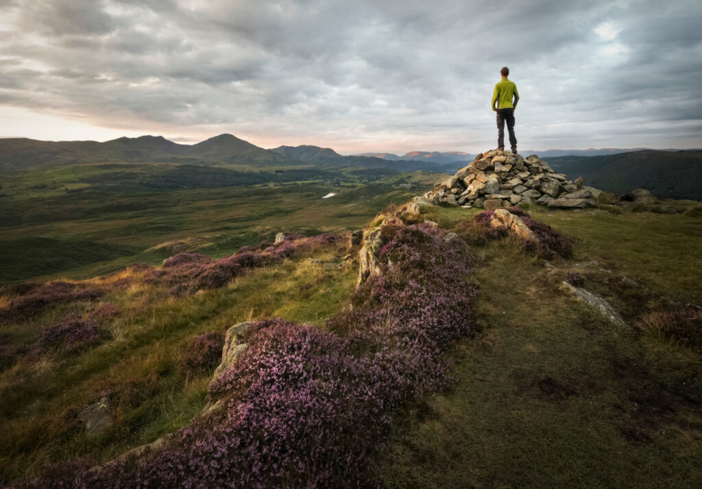 man standing on a mountain over looking the peak district landscape of mountains