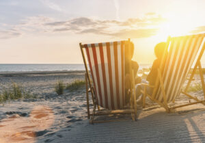 man and woman relaxing on the beach in red and white striped chairs during the sunset