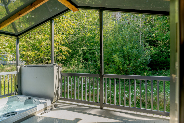 open hot tub on decking with trees around and roof above