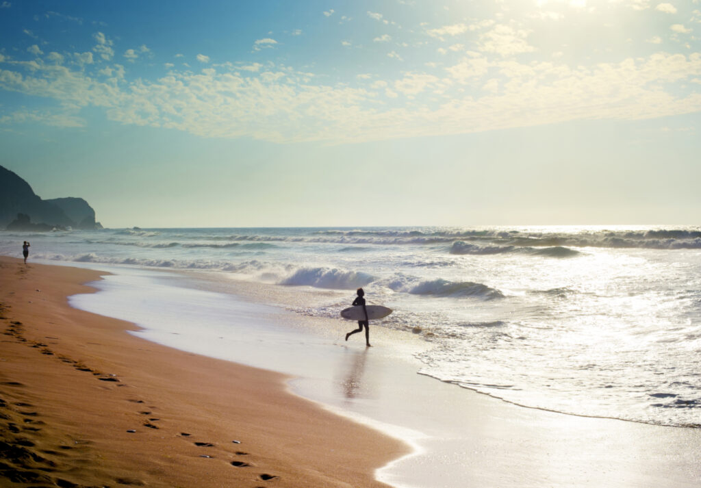 people walking towards the sea with their surfboards