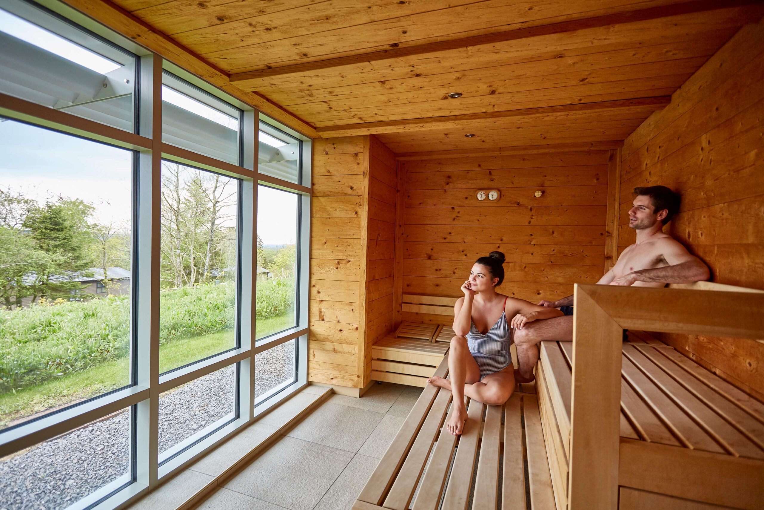 man and woman in sauna enjoying the views from the windows overlooking the lake district
