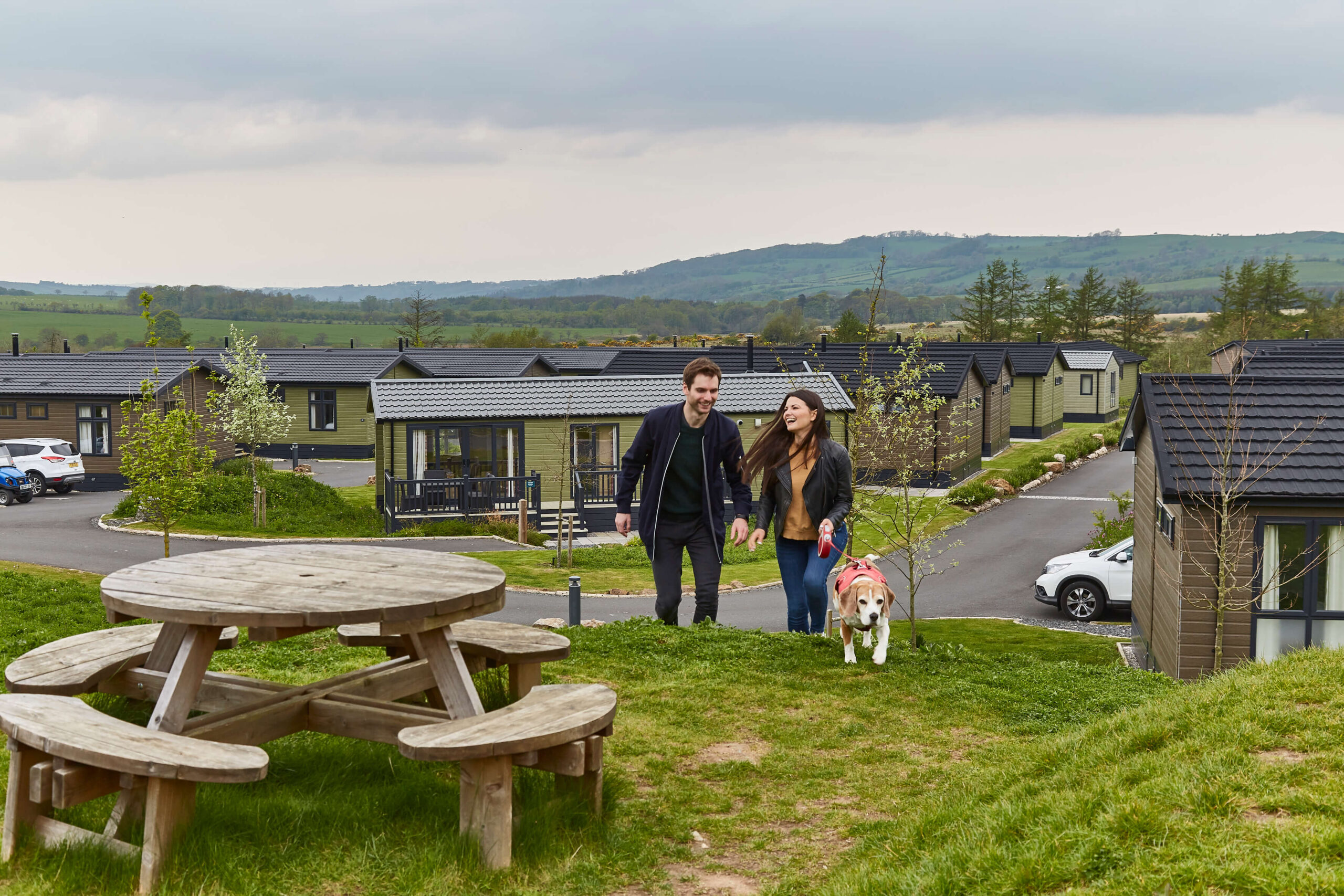 man and woman with dog walking up a hill with the resort and lodges in the back ground and a table in the front