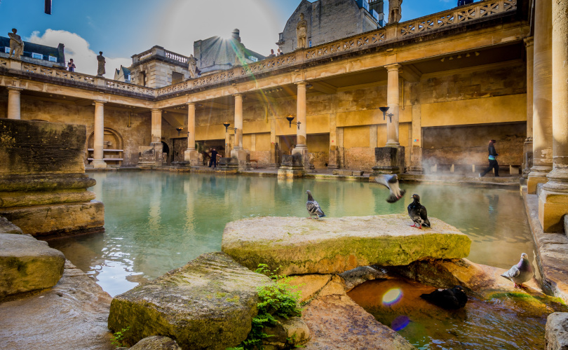 the roman baths, warm lighting and people and birds around
