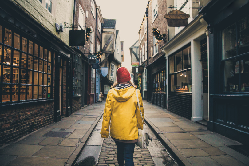 rear view of a girl walking through the shambles street in york city