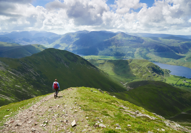 a female hiker overlooking the lake district on a sunny day
