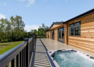 cedar-clad lodge exterior with large decking and hot tub
