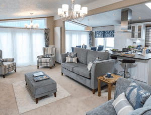 Large lodge living area with grey sofas and kitchen island
