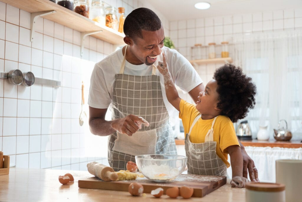 African father and son have fun in the kitchen cooking and baking together