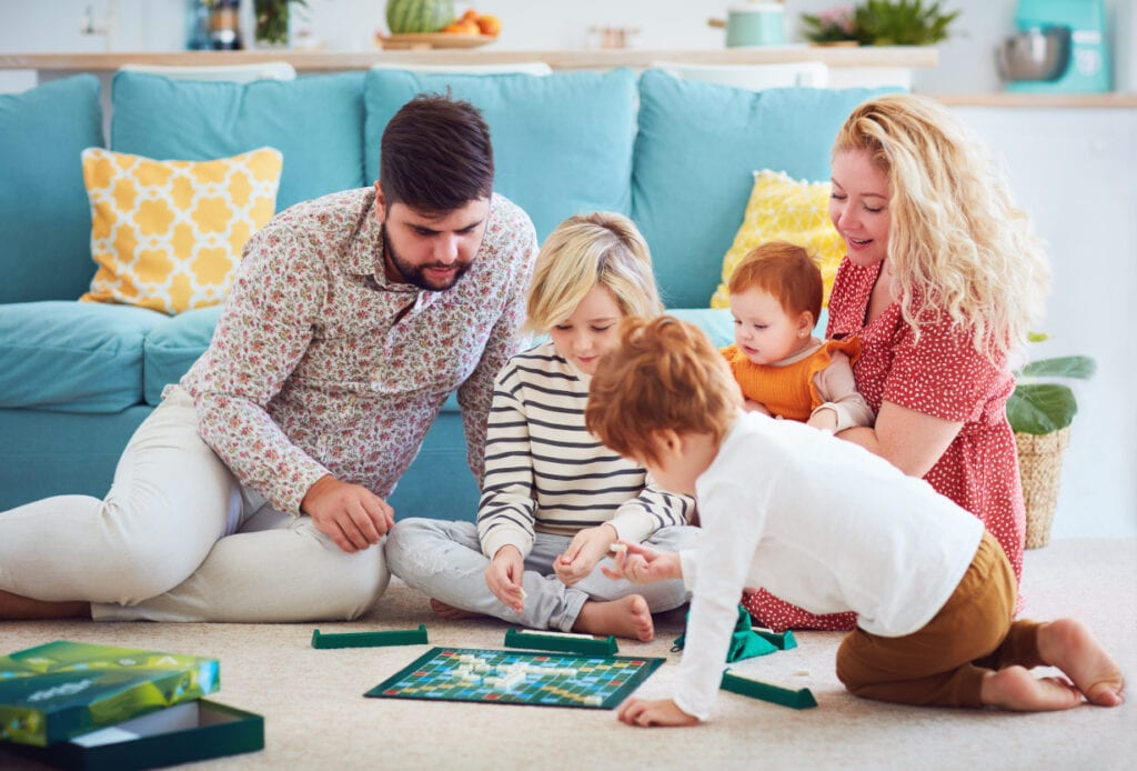 family of 5 sitting on the floor playing board games