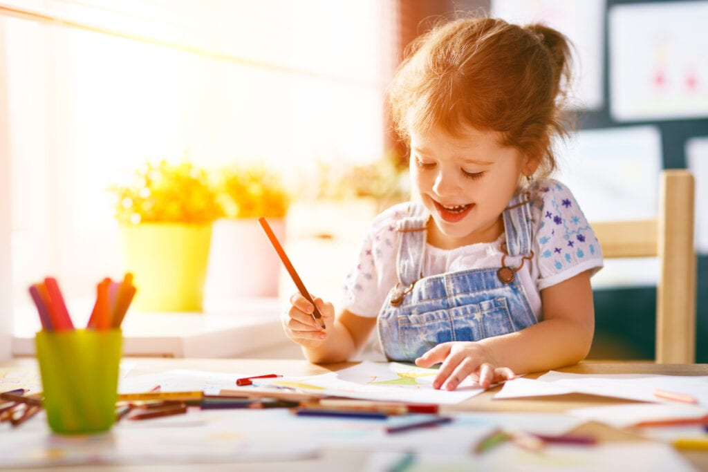 little girl colouring with pencils at the table and smiling