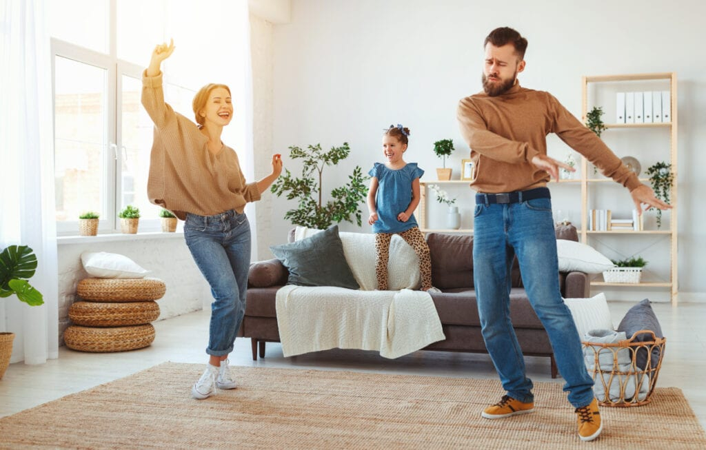 mother, father and little girl dancing in the living room