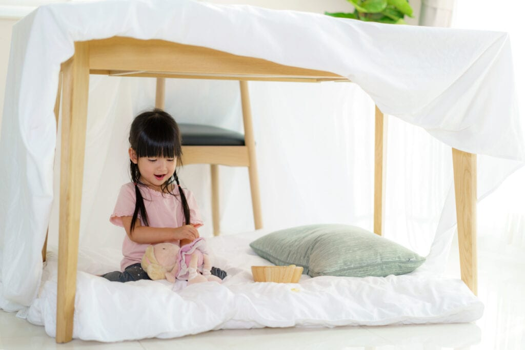 little cute Asian girl playing under the table in a den, with pillows, duvets and blankets