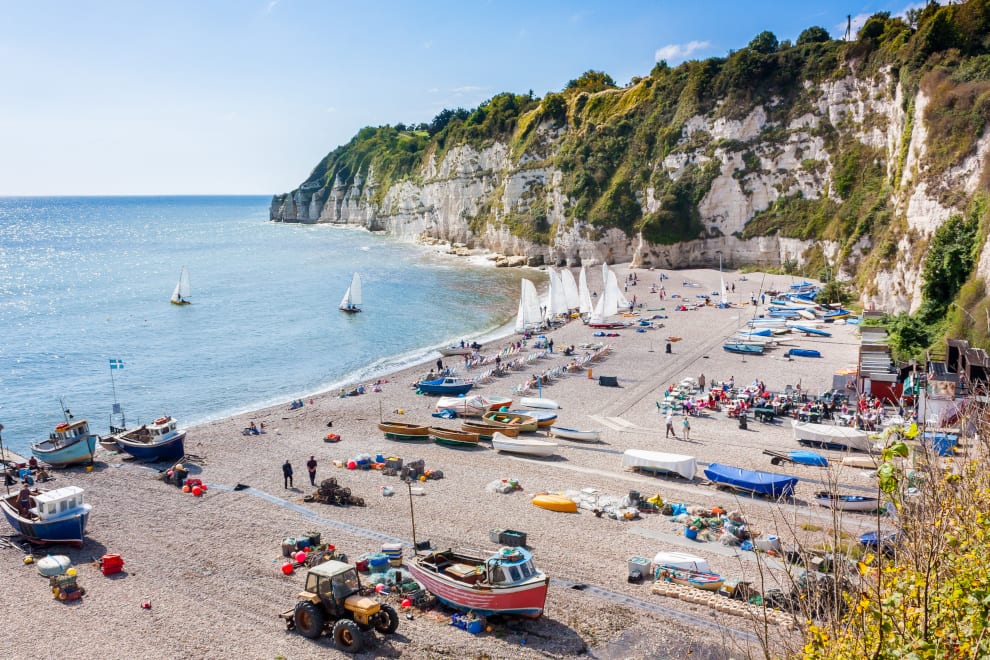 Overlooking Beer Beach, with limestone cliffs on a sunny day with boats on the beach