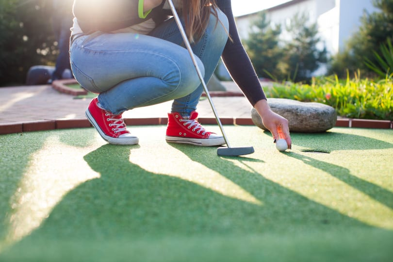 Young lady playing mini-golf. Close up of her legs and feet and she bends down to pick the ball up near the golf course hole, with golf club in the foreground.