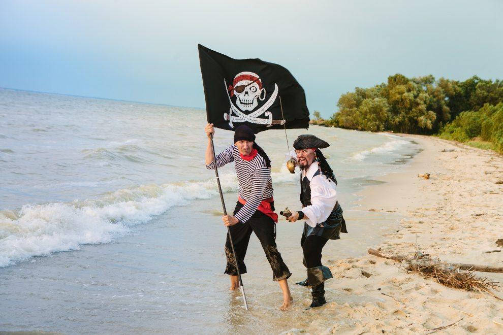 two pirates with a skull and crossbones flag on a beach on a sunny day