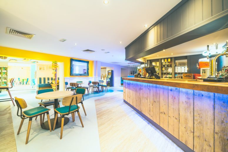 modern bar with wooden paneling, a yellow feature wall and tables of four