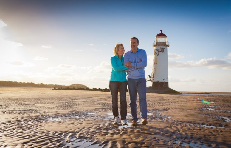 Couple in jeans and fleece tops walk on wet sand with a white lighthouse behind them