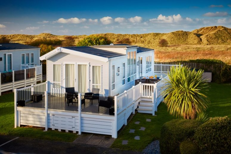 Large caravan with decking with a sand dune backdrop