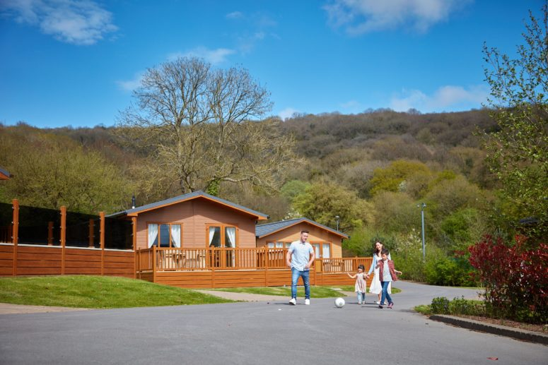 Family walking through Cheddar Woods resort with lodges in the background