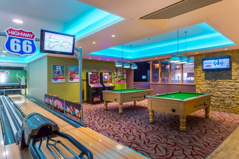 A bowling alley, pool tables and gaming machines. bright walls, feature lighting and a TV can be seen