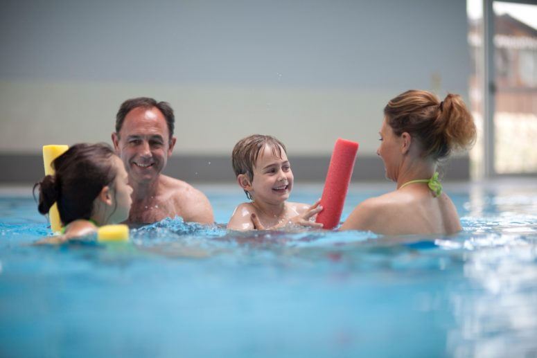 family of four play with foam pool noodles on an indoor swimming pool