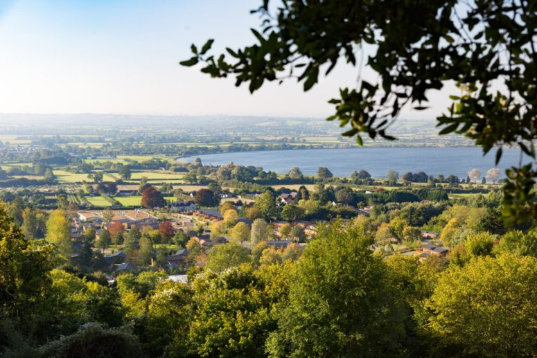 Cheddar Reservoir can be seen from the hills above. beautiful green trees and fields fill the shot
