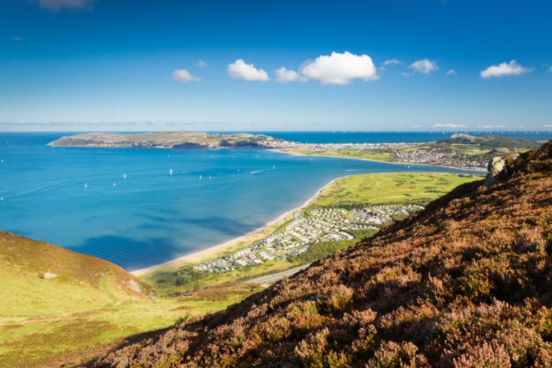 The Great Orme can be seen from Conwy Mountian. We look down on blue sea, the tide is in and yachts can be seen. We see a caravan park (aberconw) from a birds-eye-view