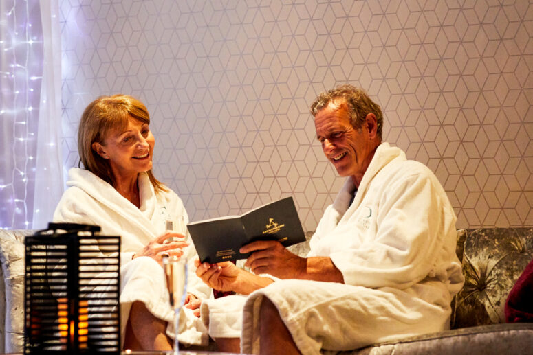 man and woman relaxing in spa bathrobes while looking at spa menu