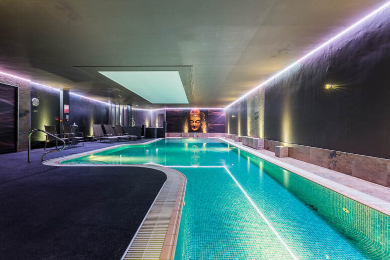 Indoor pool with purple mood lighting. Lounger are around the side and an image of a buddha is on the wall